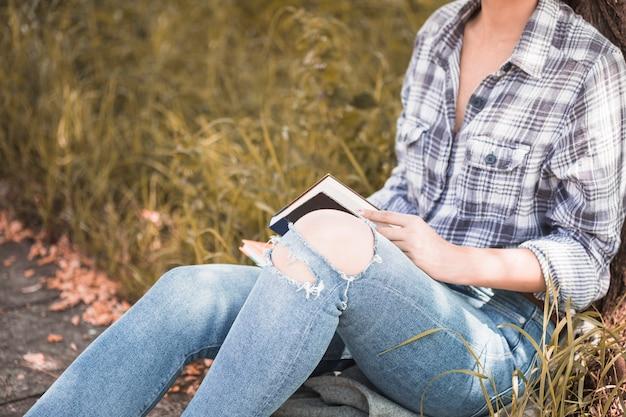 Femme assise sur l'herbe et tenant le volume