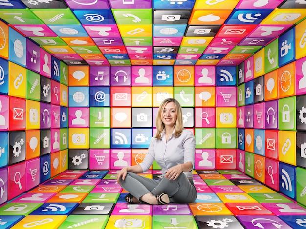 Femme assise à l'intérieur d'une pièce faite de cubes avec des icônes de couleurs différentes