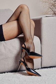 Femme assise jambe par jambe dans des chaussures à talon ouvert sur un canapé (image recadrée)