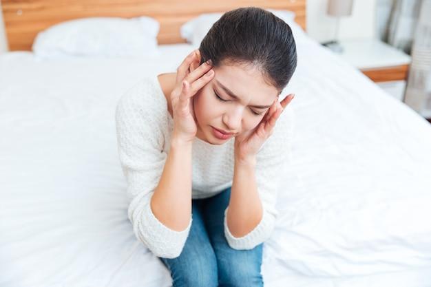 Femme assise sur le lit et ayant mal à la tête à la maison