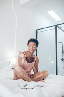 Une femme assise sur le lit et prenant son petit déjeuner