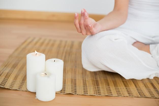 Femme assise en lotus pose à côté des bougies blanches