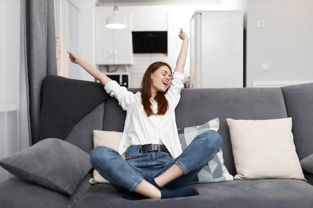 Femme assise avec les mains levées vers le haut sur le canapé