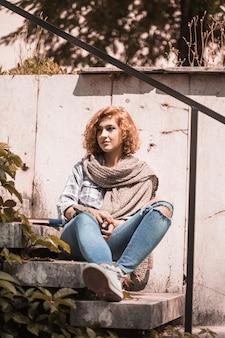 Femme assise sur les marches du jardin public