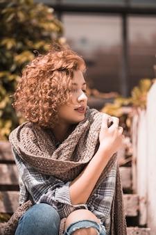Femme assise sur les marches et tenant une écharpe