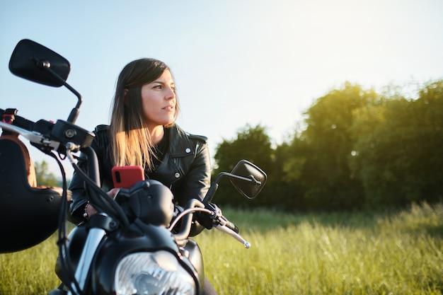 Femme assise sur une moto à la campagne au coucher du soleil