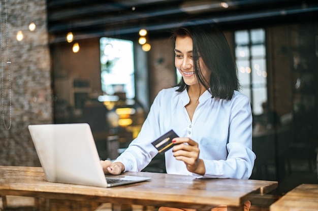Femme assise avec un ordinateur portable et payée avec une carte de crédit dans un café