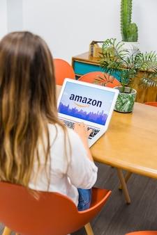 Femme assise avec un ordinateur portable près de la table