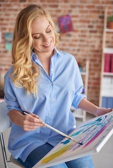Femme assise et peinture en studio de design