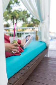 Femme assise sur la piscine de la station et de boire du jus