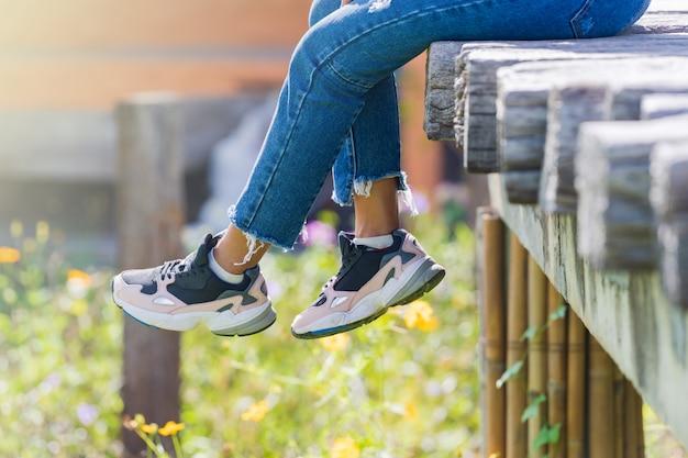 Femme assise sur le pont en bois et jambes suspendues dans le jardin fleuri