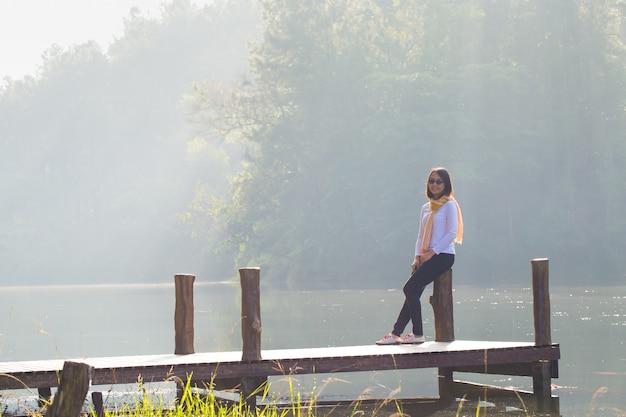 Femme assise sur un pont en bois