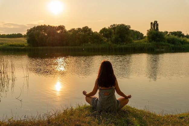 Femme assise en position du lotus en méditation sur une colline surplombant le paysage rural au coucher du soleil