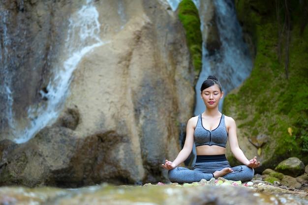 Femme assise en position de lotus zen en faisant des gestes. concept de mode de vie sain et de détente.