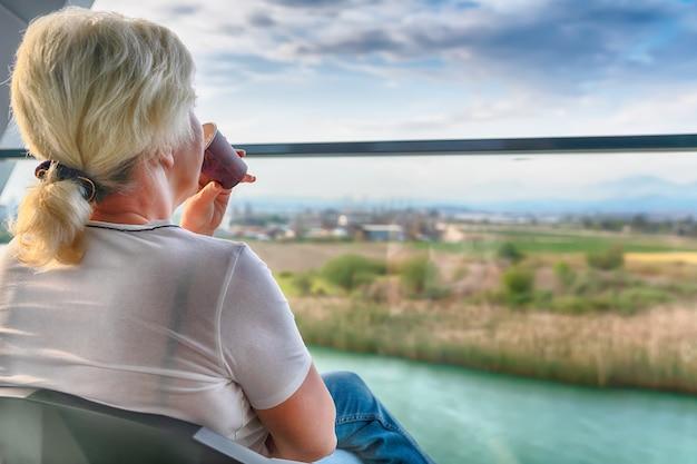 Femme assise en prenant un verre sur une terrasse extérieure