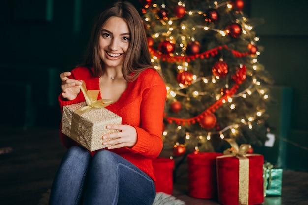 Femme assise près d'un arbre de noël et déballage du cadeau de noël