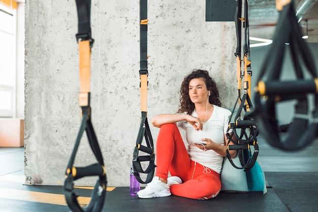 Femme assise près de la courroie de fitness, écouter de la musique sur téléphone mobile