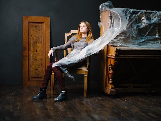 Femme assise près du piano sur un instrument de musique romance intérieur chaise