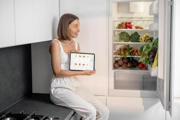 Femme assise près du réfrigérateur plein de légumes frais, tenant une tablette numérique avec une application e-shop en cours d'exécution. concept d'achat de nourriture en ligne
