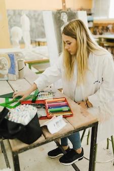 Femme assise près de l'établi avec beaucoup de crayons de couleur