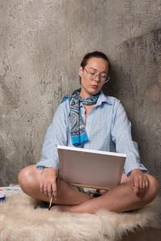 Femme assise et regardant sur toile avec pinceau sur marbre