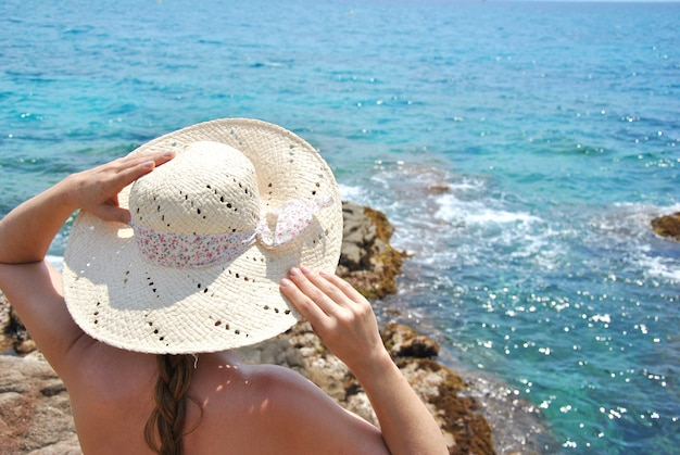 Femme assise sur des rochers en regardant l'horizon avec son chapeau