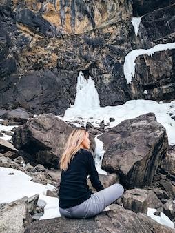 Femme assise sur les rochers