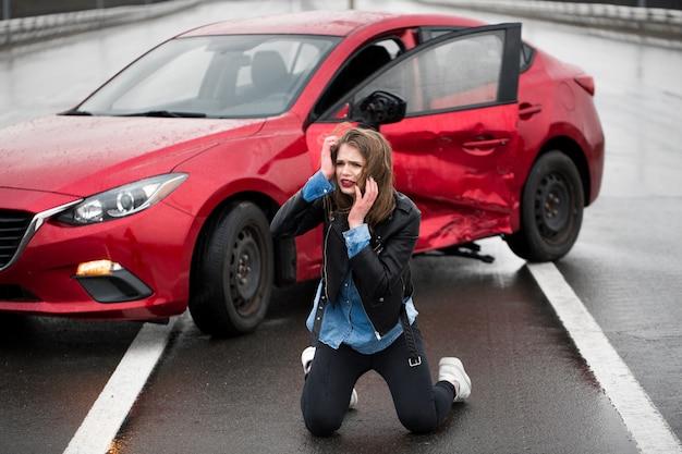 Femme assise sur la route après un accident de voiture