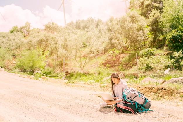 Femme assise sur la route et en train de taper sur un cahier parmi des sacs à dos