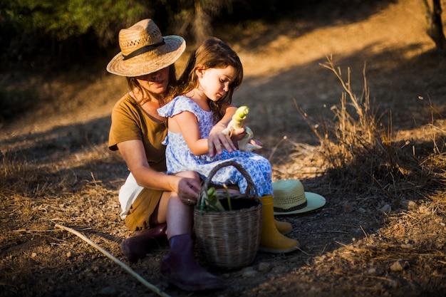 Femme assise avec sa fille dans le champ