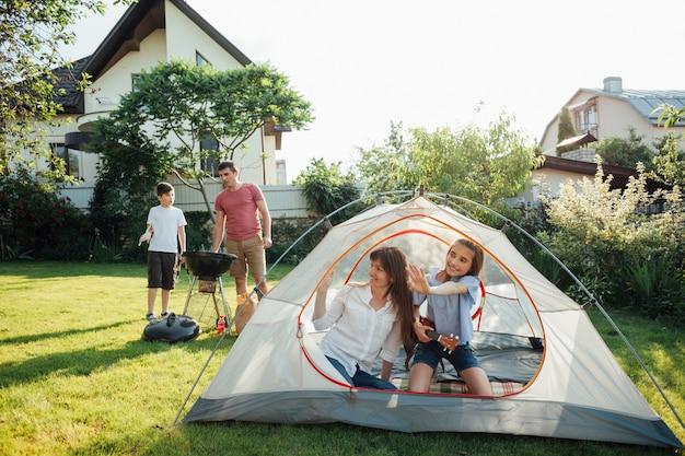 Femme assise avec sa fille dans la tente pendant que son mari et son fils cuisinent sur un barbecue
