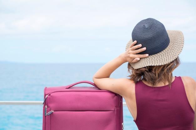 Femme assise avec sa valise, imaginant son prochain voyage.