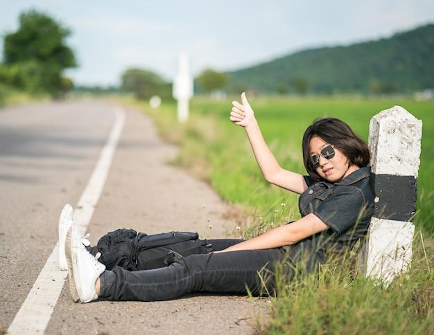 Femme assise avec sac à dos auto-stop le long d'une route dans la campagne