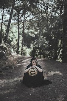 Femme assise se penchant sur le potiron dans le parc