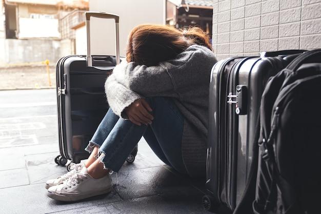 Une femme assise avec un sentiment de tristesse en voyageant avec beaucoup de bagages sur le sol