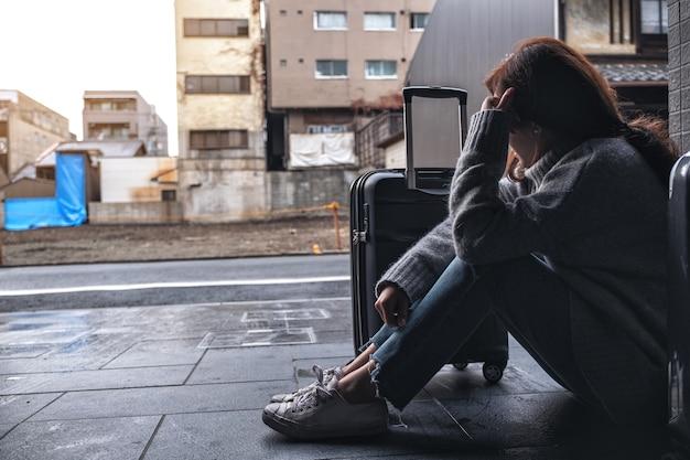 Une femme assise avec un sentiment de tristesse en voyageant avec beaucoup de bagages