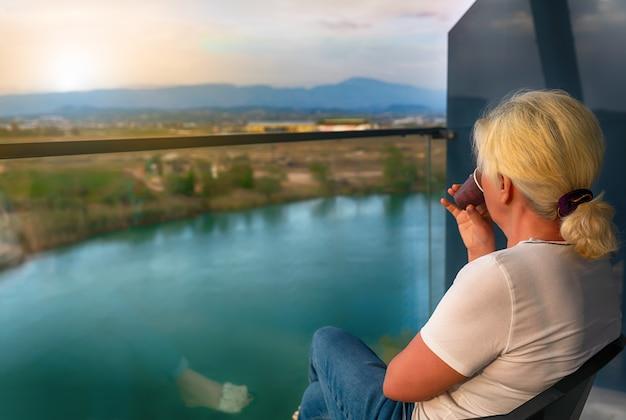 Femme assise en sirotant un café sur un balcon au lever du soleil