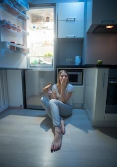 Femme assise sur le sol de la cuisine à côté d'un réfrigérateur ouvert et mangeant une pizza