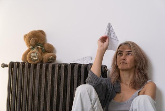 Une femme assise sur le sol dans son appartement regarde un avion fait d'une feuille de papier avec des notes qu'elle tient dans sa main
