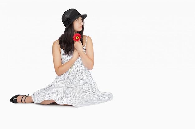 Femme assise sur le sol en détournant les yeux