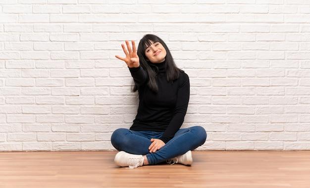 Femme assise sur le sol heureuse et comptant quatre avec les doigts