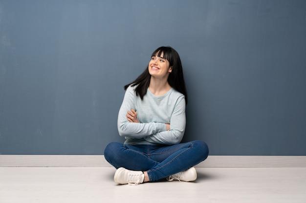 Femme assise sur le sol, heureuse et souriante