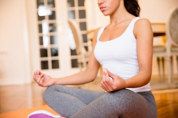 Femme assise sur le sol à la maison faire du yoga méditation