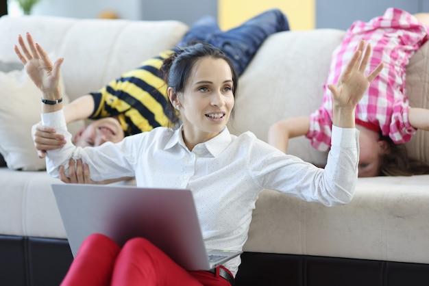 Femme assise sur le sol avec un ordinateur portable