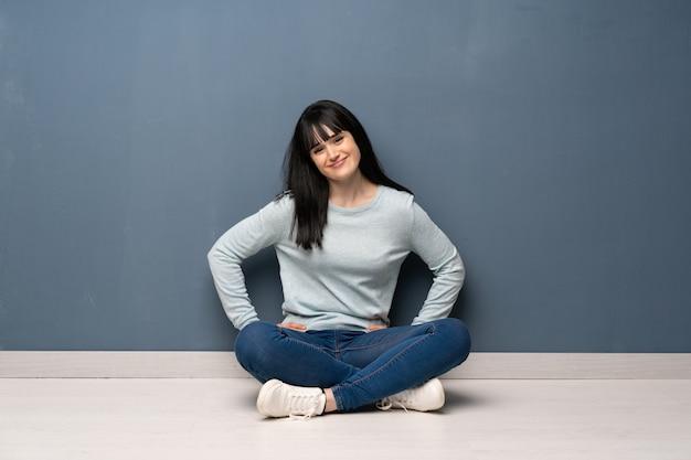 Femme assise sur le sol, posant avec les bras à la hanche et souriant