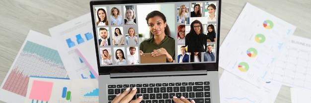 Femme assise sur le sol près de documents et communiquant par liaison vidéo avec l'équipe d'employés vue de dessus