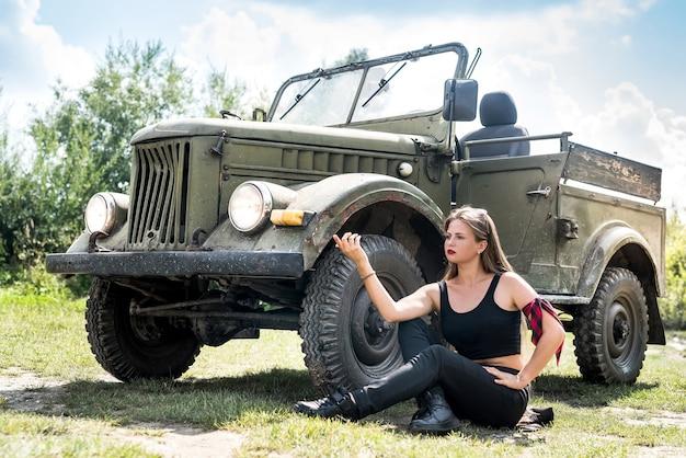 Femme assise sur le sol près de la voiture militaire
