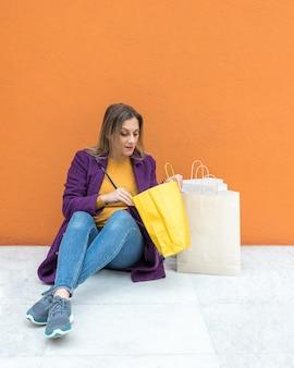 Femme assise sur le sol à la recherche de sacs à provisions