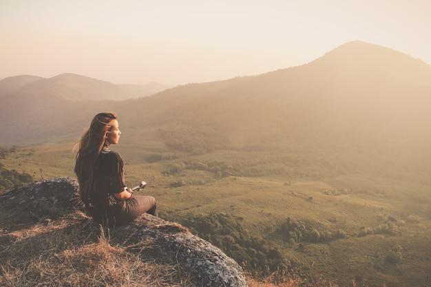 Femme assise sur le sol regardant au coucher du soleil