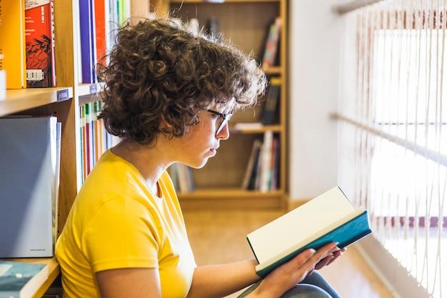 Femme assise sur le sol, s'appuyant sur la bibliothèque